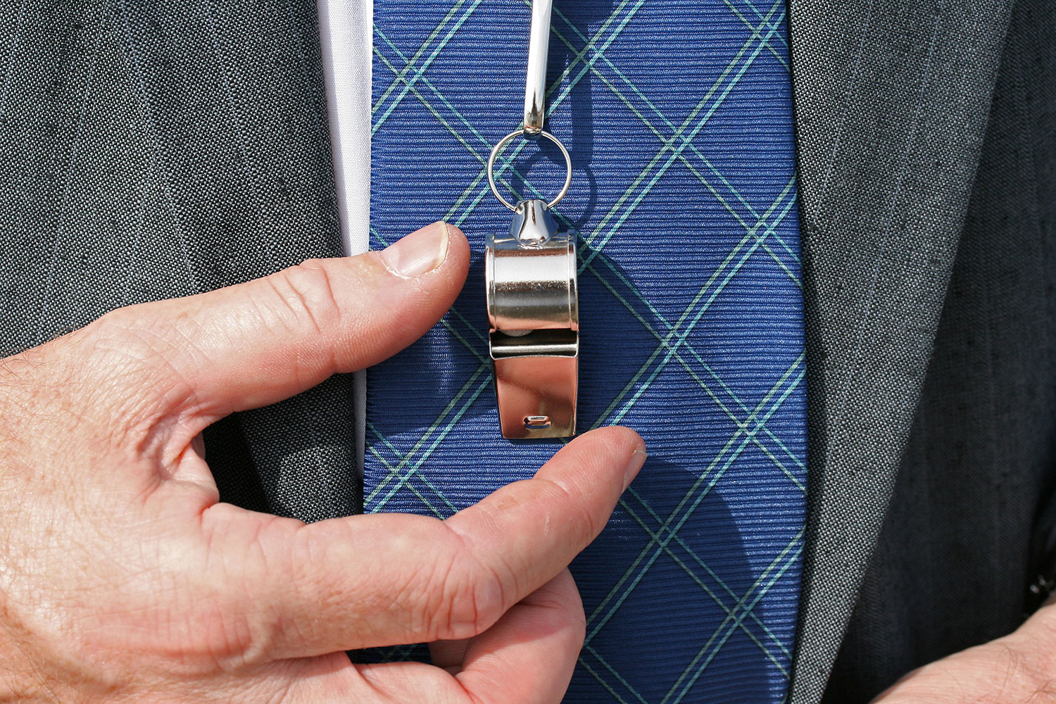 man's suit and tie with his hand grabbing a coach's whistle