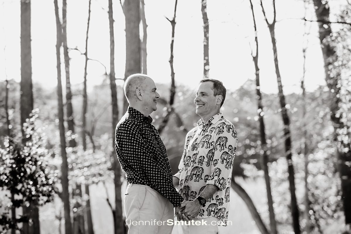 two men holding hands and laughing