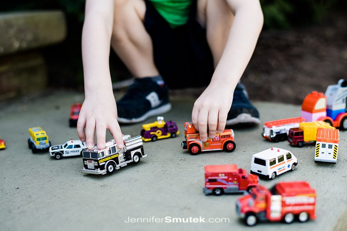 kid's arms playing with toy trucks
