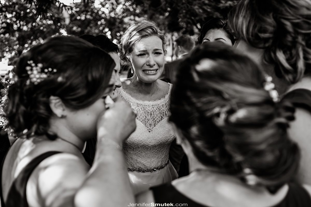 bridesmaids hugging bride while crying happy tears