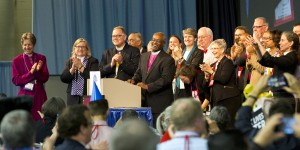 Presiding Bishop-elect Michael Curry, bishop of the Diocese of North Carolina, speaks to a packed House of Deputies hall after deputies confirmed his election as the 27th presiding bishop of The Episcopal Church. Curry's family and others joined him on the dais. (Photo: Cynthia L. Black/ENS)