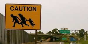 Sign located near the border between California and Tijuana along the Via de San Ysidro warning motorists of families potentially fleeing from border crossing checkpoints. (Photo credit:  Zilia Castrillon/Flickr)