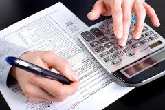 accountant working with a calculator and a tax form