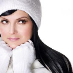 young woman wearing white gloves and a white knit hat