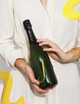 Woman holding a bottle of J sparkling wine.