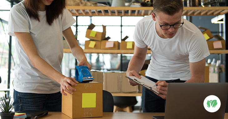 Two workers packing boxes for shipment