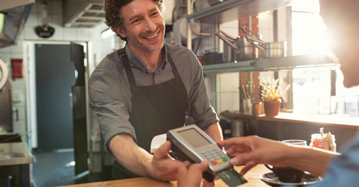 Male shop keeper accepting credit card payments