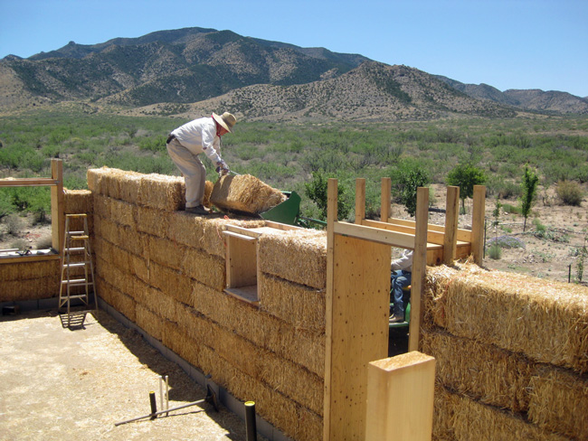 Dave loads bales on the strawbale house, with a little help from a big green tractor.