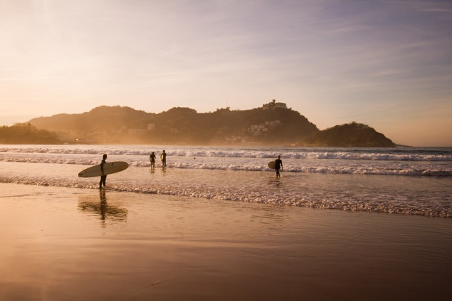 Surfers at dusk in San Sebastian, Spain