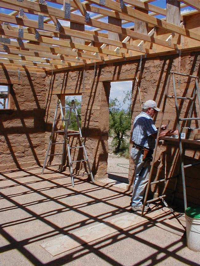 Dave under the newly-installed roof trusses of the adobe cottage.