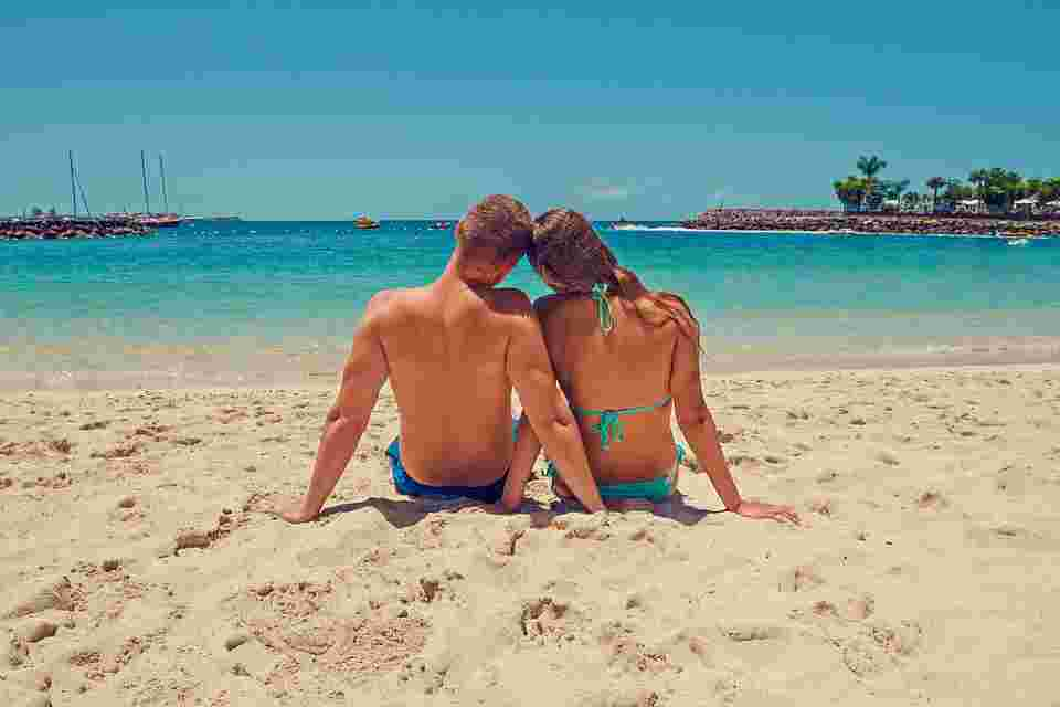 a couple at the beach getting exposed to sunlight to increase their deep sleep quality and quantity