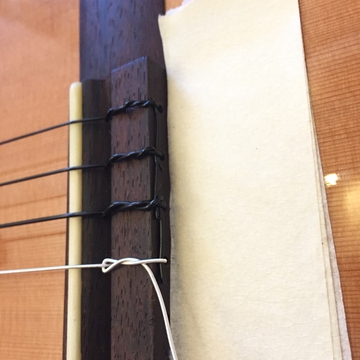 1弦側から余った部分を重ねて縛る