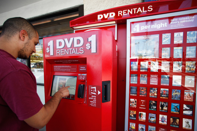 A customer renting a movie from a Redbox kiosk