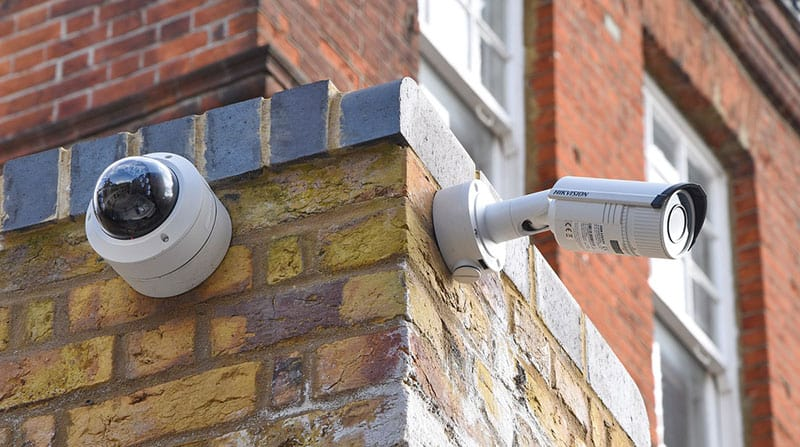 image of two CCTV cameras mounted on an external brick wall of a commercial property
