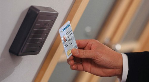 Image of an employee swiping a key card across the reader base next to a door.