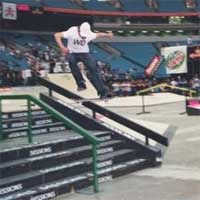 Skateboarder pulls off sick railslide at 2004 Slam City Jam.
