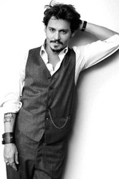 Johnny Depp wears a three-piece suit minus the jacket. The pocket watch chain and cuffed sleeves personalize the look.
