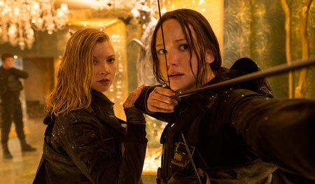 Katniss takes aim while Cressida looks on