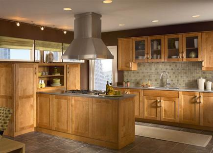 A kitchen with warm maple cabinets, gray counters and gray tile flooring.