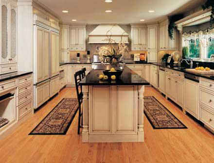 A white kitchen with black counters, a large island, and plenty of room to walk around.