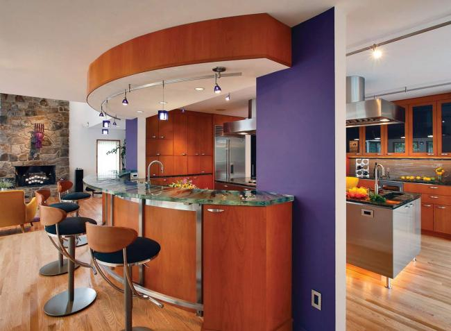 This warm contemporary kitchen combines stainless steel and alder veneer cabinets with oak flooring and a bright purple wall