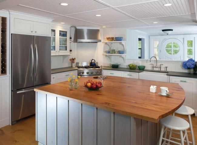 A New England kitchen with white cabinets and wood flooring