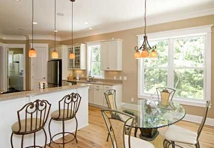 A white kitchen with pendant lights, recessed lights and undercabinet lights.