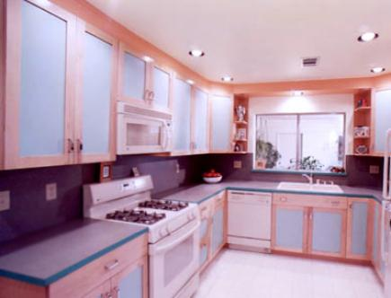 U-shaped kitchen with light cabinets and white appliances.