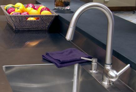 A single hole faucet high-arc spout, lever handle and soap dispenser.