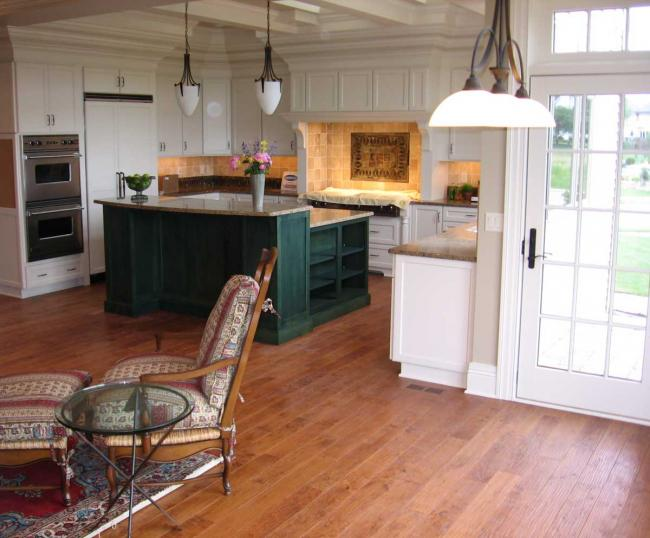 White country kitchen with dark green island and cherry flooring
