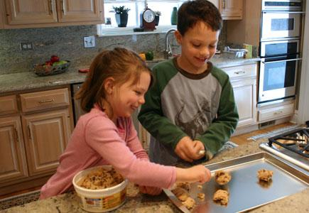 Two small children helping to cook in a kitchen