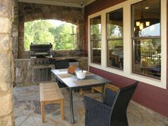 Small outdoor kitchen with grill, table and bench.