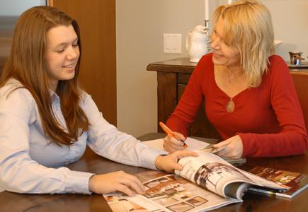 Young woman going through magazines with a designer