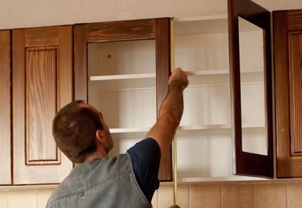 Man refacing wooden cabinets.