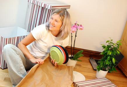 A woman packs up dishes during a remodeling