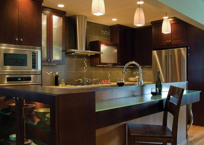 A kitchen with floating cherry cabinets, and an island with a sandblasted glass dining bar