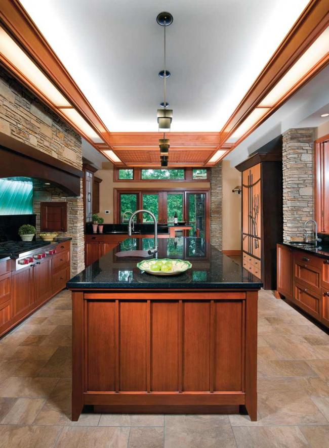 An Arts & Crafts style, Frank Lloyd Wright inspired kitchen with wood cabinets, stone floors and a glass backsplash