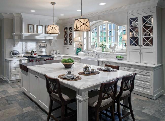 A large white kitchen with marble counters, limestone flooring, a Wolf range and a kitchen island