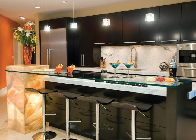 Kitchen with cherry cabinets, marble counters, backlit onyx pedestal and orange wall