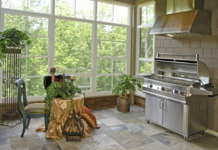 Grill with ventilation hood in outdoor kitchen on a porch.