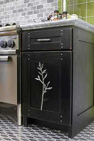 Dark wood cabinet with large silver branch as hardware.