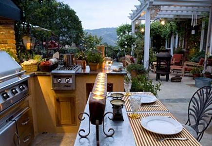 Outdoor kitchen with grill, burners, counter, pergola and lounge chairs.
