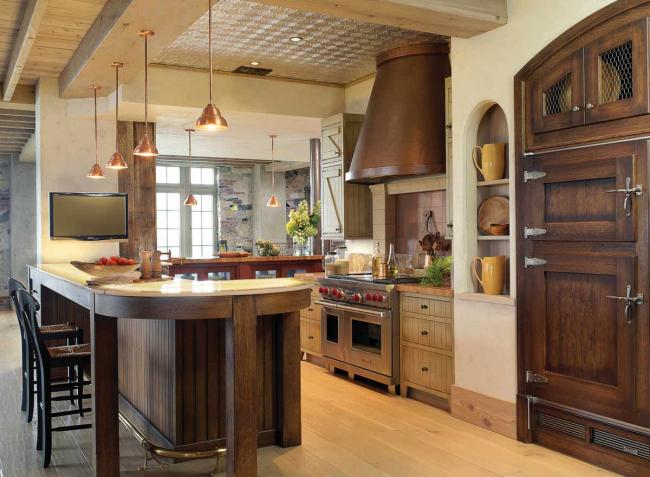 A farmhouse style kitchen with wood cabinets, an onyx counter, copper vent hood and tin ceiling