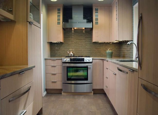 A small kitchen with white oak cabinets, integrated appliances and a green tile backsplash