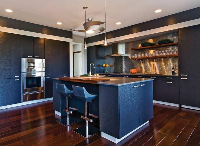 A contemporary gray kitchen with stainless steel appliances and a stainless steel backsplash