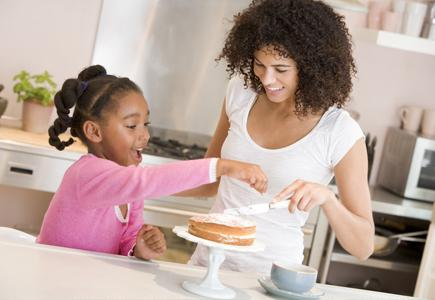 Woman and girl making cake in kitchen