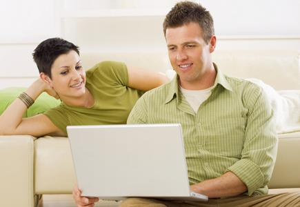 Couple in Green Shirts Looking at Computer