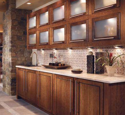 A kitchen with dark cherry cabinetry and light stone counters and floors.
