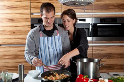Couple cooking together in modern kitchen.
