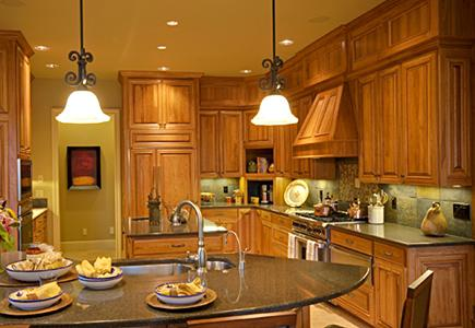 Warm wood kitchen cabinets with quartz counters and stainless steel appliances.